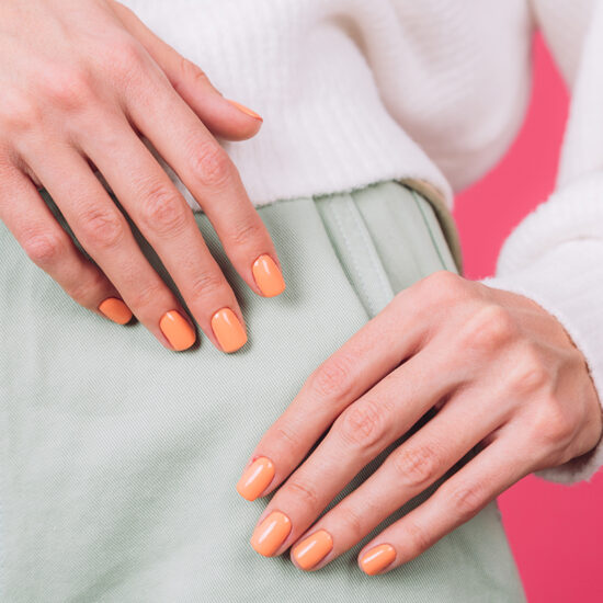 close frame of woman's hands with orange manicure on white sweater and pink background isolated copy space